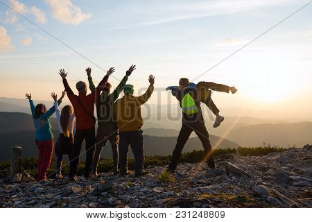 Joyful Hikers, Friends With Open Arms Are Standing On A Top, Admiring The Panorama Of Mountains In T