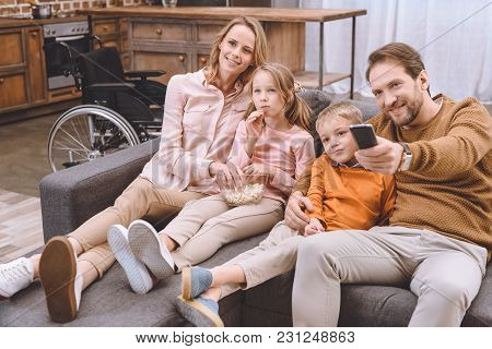 Happy Family Sitting On Sofa And Watching Tv Together And Wheelchair Standing Behind