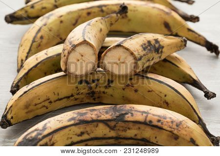 Whole and half fresh raw yellow plantains