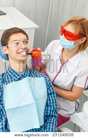 Beautiful Woman Dentist Treating Teeth In Dental Office. Doctor Wearing Glasses, Mask, White Uniform