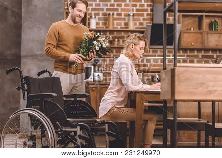 Side View Of Disabled Woman Taking Notes And Smiling Man Holding Bouquet Of Flowers At Home