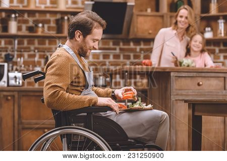 Side View Of Smiling Man In Wheelchair Cutting Vegetables For Salad While Happy Mother And Daughter