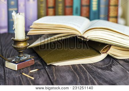 On The Wooden Background Of The Table There Are Stacks Of Colorful Books Near The Old Candlestick Wi