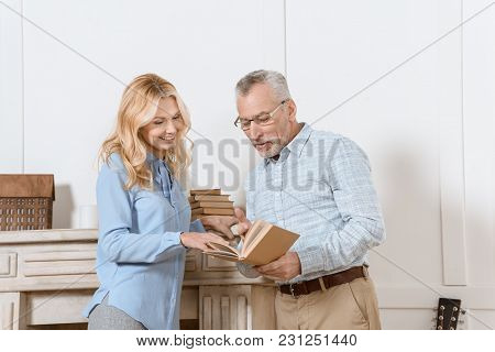 Mature Woman And Man Reading Book Together By Fireplace In Light Room