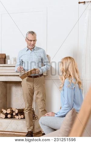 Mature Man Reading Book And Discussing It With Woman In Light Room