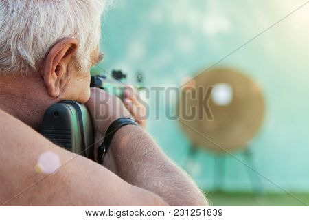 Gray-haired Man Aiming From A Rifle At A Straw Target