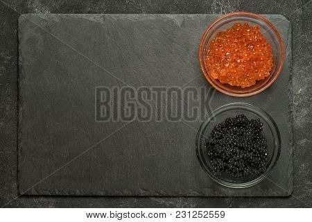 Red Salmon And Black Stugeon Caviar In The Side Of Black Stone Board On A Black Table, Top View With