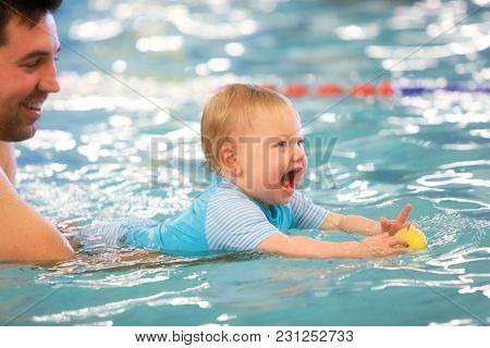 A father helps is infant daughter during swimming lessons in the pool.