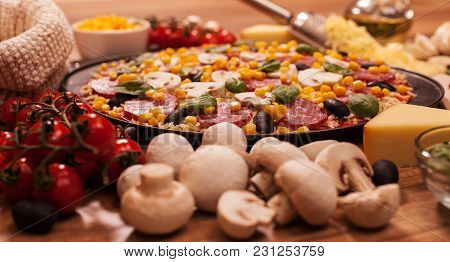 Fresh Homemade Pizza On A Table With Ingredients Around - Closeup