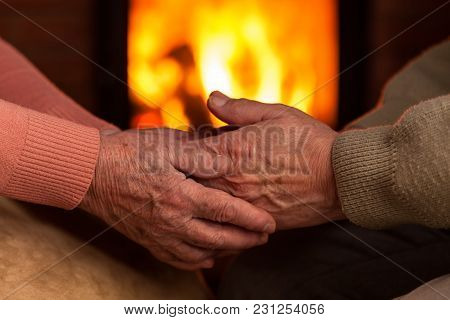 Senior Old Hands Comforting Each Other In Front Of Fireplace - Together Forever Concept