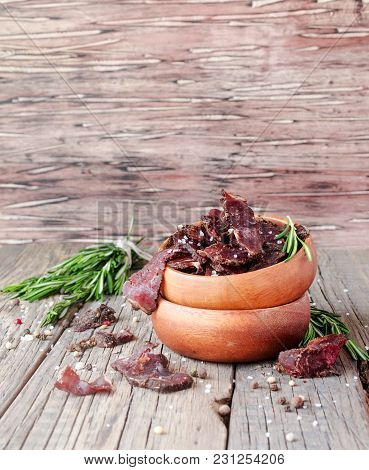 Jerked Dried Meat, Cow, Deer, Wild Beast Or Biltong In Wooden Bowls On A Rustic Table, Selective Foc