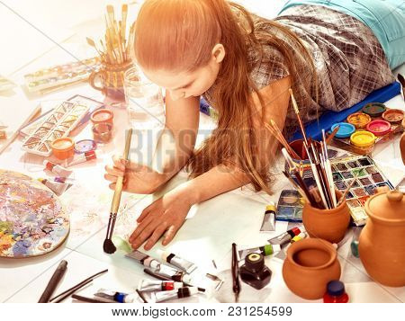 Authentic artist children girl paints with set palette watercolor paints palette and brush in morning sunlight. Painting in studio on floor. Child is forced to draw.