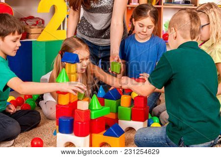 Children building blocks in kindergarten. Group kids playing toy on floor. Top view of interior preschool. Building a tower of cubes. Newcomer in a children's team.