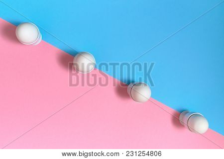 White Eggs Standing On Egg Cup On Blue And Pink Pastel Background, Copy Space. Row Of Boiled Egg In