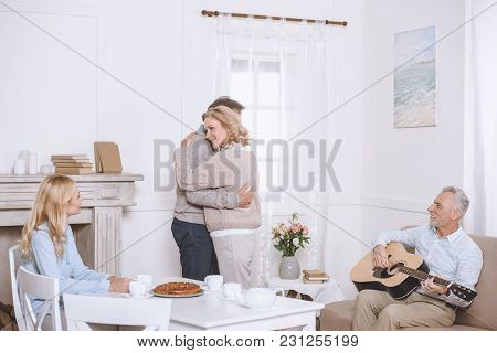 Elder Man Playing Guitar While Friends Spending Tme And Dancing In Room