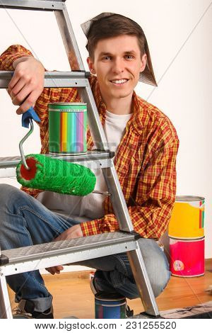 Repair home man holding paint roller for wallpaper. Tired and frustrated male in newspaper cap renovation apartment. Paint bank and roll paper background on isolated. Stepladder in foreground.