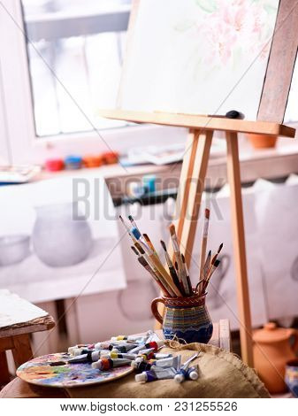 Authentic paint brushes still life on table in art class school as drawing course. Cropped shot of group of brush in clay jar. Discounts on goods for artists. Easel for still lifes.