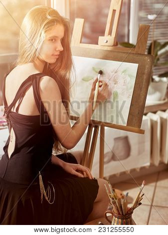 Artist painting on easel and palette in studio. Authentic girl paints with oil brush morning sunlight dawn light toning window background. Quiet environment for creativity. Sun flare drawing homework