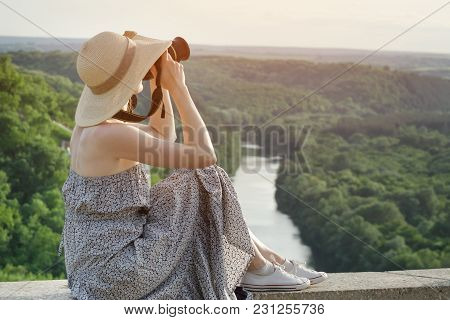 Side View Of A Girl With A Camera. View From A Hill On A Green Forest And River