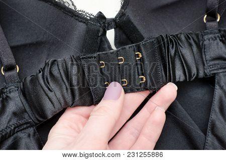 Fasteners Black Bodice In A Female Hand. Fashionable Concept