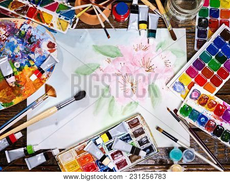 Authentic paint brushes still life in art class school. Group of brush in clay jar. Bouquet of tulip flowers as symbol of spring discounts. Copy space for text. Courses on drawing for children.