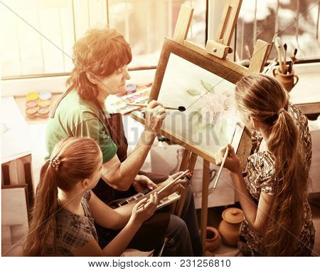 Artist painting easel in studio. Authentic grandmother and kids girl paints with palette watercolor paints palette and brush morning sunlight. Handmade crafts warm-glow of school teacher in drawing.