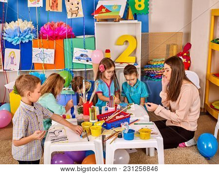 Small students with teacher painting in art school class. Child drawing by paints. Craft drawing education develops creative abilities of children. Art children's school.