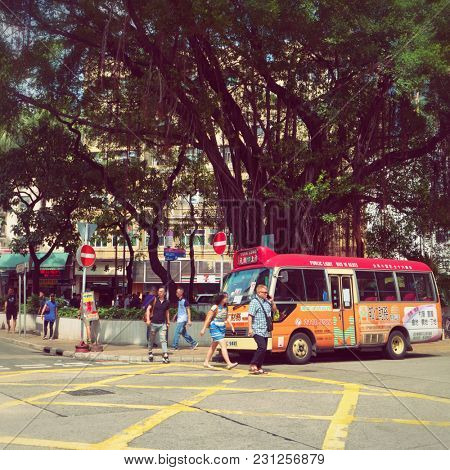 Hong Kong - October 2017: Street view with people, minibus and big banyan tree. New Territories.