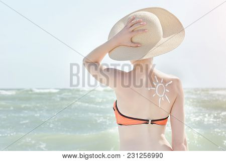 Girl In A Hat Against Sea. On The Back Is Painted Sun