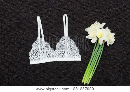 White Lace Bra And Bouquet Of Daffodils On A Black Background. Fashionable Concept