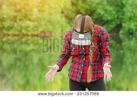 Girl In The Helmet Of Virtual Reality Against The Background Of Nature. Looking Down
