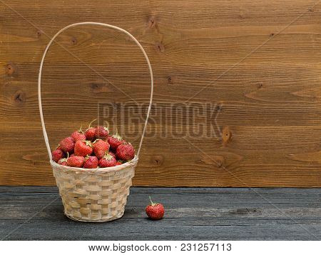 Basket Of Ripe Strawberries On A Black Table, Wooden Background. Space For Text