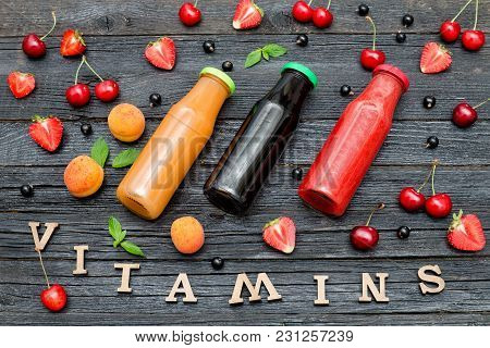 Three Bottles Of Juice, Fruit And Inscription Vitamins. Wooden Background.