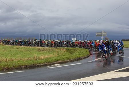 Cernay-la-ville, France - March 5, 2017: The Peloton Taking A Curve On A Wet Road During The First S