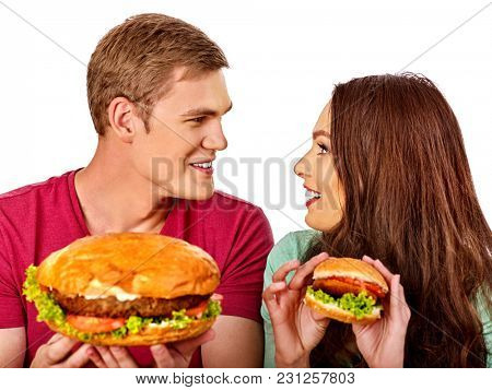 Couple eating fast food. Man and woman eat hamburger with ham. Friends holding burders junk on isolated. Loving couple prefers fast food to homemade dinner. Health problems due to malnutrition.