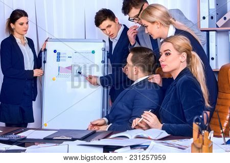 Business people office life of team people working with papers sitting table. Schemas and diagrams on presentation and demonstration. Firm is considering proposed contract.