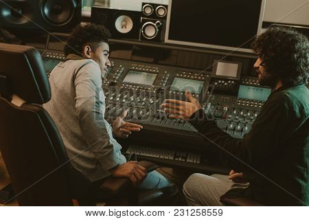 View Of Young Musicians Talking At Recording Studio