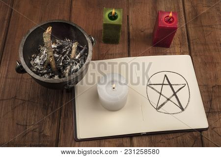 A Photo Of A Candle, A Witch's Cauldron, And A Pentacle In A Book Of Shadows