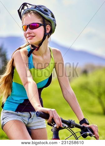 Woman traveling bicycle in summer park. Womens road bike for running on green grass aganist blue sky with white clouds. Female in school trip. Girl keeps herself in good shape.
