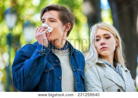 Man with cold rhinitis on autumn outdoor. Fall flu season. Girl looks with compassion on suffering of loved one. Disease spoiled rendezvous.