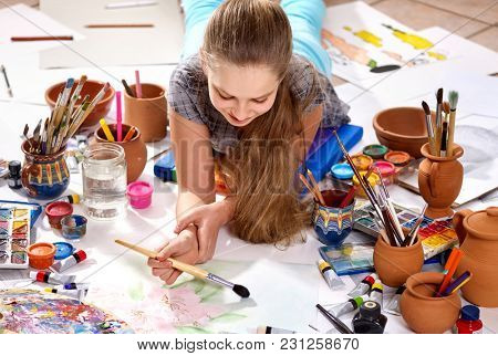 Authentic artist children girl paints with set palette watercolor paints palette and brush in morning sunlight. Painting in studio on floor. Home interior handmade crafts. Competition on drawing.