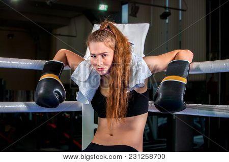 Girl wearing black gloves sitting in corner of boxing ring. Martial arts for sportswoman do fitness.