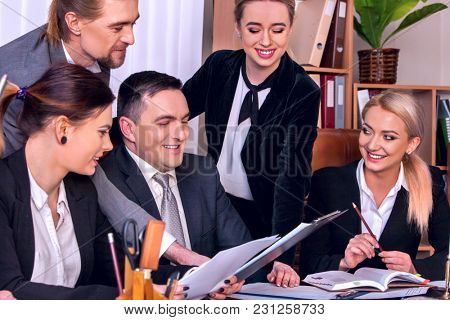 Business people office life of team people working with papers sitting table. Cabinets with folders and jalousie, flowers in pots background. Firm increased its revenues for year.