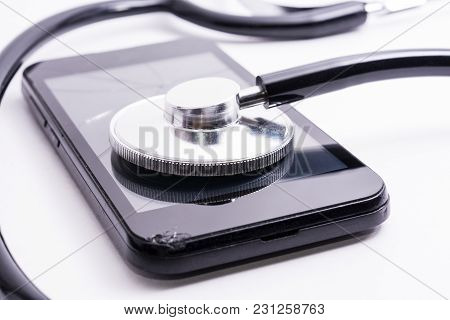 Old Crushed Mobile Phone With A Broken Screen And A Stethoscope On A White Background. Concept Of Mo
