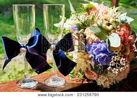 Two Empty Wedding Champagne Glasses With Blue Ribbon Bow And Bridal Bouquet Outdoors In Summer Day,