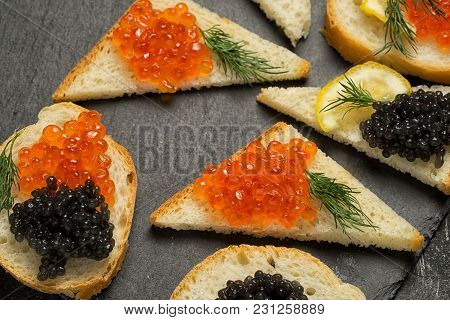 Sandwiges With Red Salmon And Black Stugeon Caviar On A Black Background, Top View.
