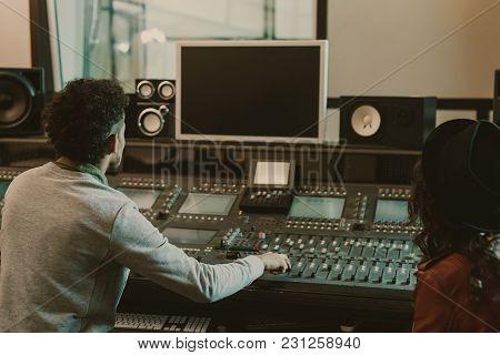 Sound Producers Looking At Blank Monitor At Recording Studio