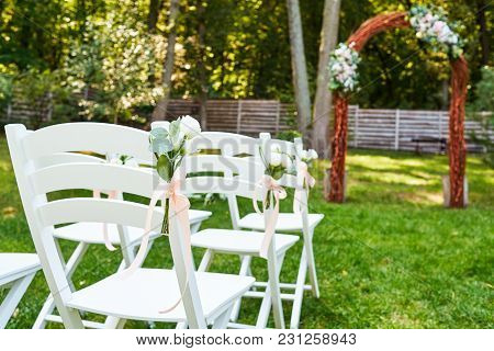 White Fresh Flowers With Pink Ribbon On Wedding Chair On Each Side Of Archway Outroods; Copy Space.