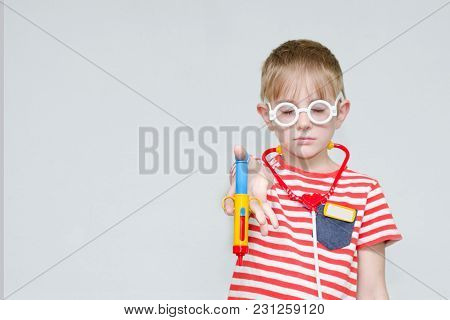 Sad Boy With A Toy Syringe In Glasses