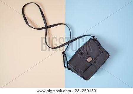 Fashionable Concept. Black Handbag. Tender Beige And Blue Background.